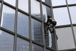 Alain Robert lezie na 48-poschodový mrakodrap Tour Total v Paríži.