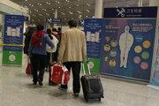 Cestujúci kráčajú okolo kontrolného stanovišťa zdravotného stavu na letisku v Pekingu.