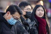 Cestujúci v blízkosti železničnej stanice v Pekingu.