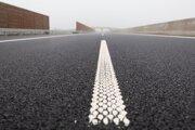 Stredové vodorovné dopravné značenie a stavba rýchlostnej cesty R7 počas sprevádzanej ukážky aktuálnych prác na najväčšej trvajúcej dopravnej stavbe v strednej Európe D4R7 neďaleko obce Veľká Paka 12. decembra 2019.