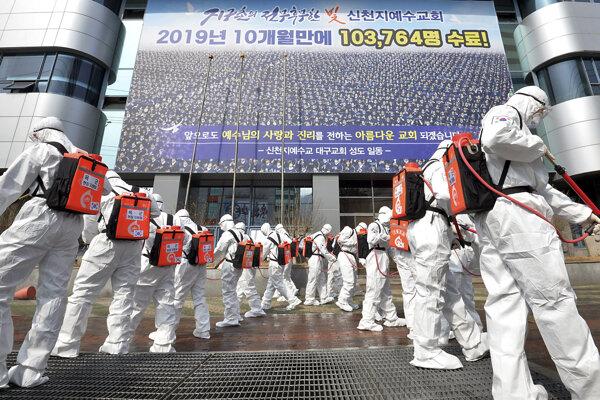 Vojaci v ochranných odevoch používajú dezinfekčný sprej, aby zamedzili šíreniu koronavírusu. Daegu, Južná Kórea,  1. marec 2020.