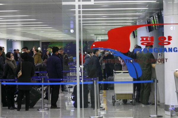 Cestujúci na letisku v Pjongčangu.