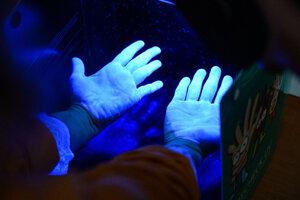 Kontrola rúk pod lampou, ktorá vyžaruje ultrafialové žiarenie po ošetrení dezinfekčným gélom počas praktickej ukážky hygieny rúk v rámci školenia pre zníženie rizika šírenia nebezpečných nákaz.