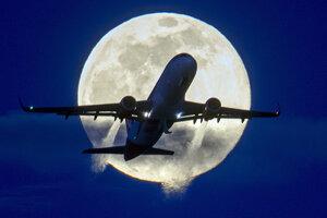 Stúpajúce lietadlo prechádza pred Mesiacom v splne.
