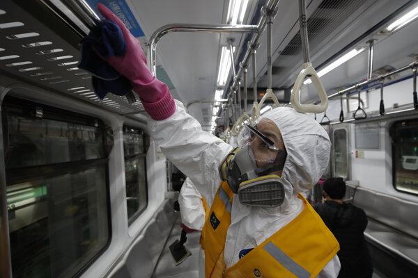 Pracovník v ochrannom obleku dezinfikuje vagón metra proti koronavírusu v Soule, Južná Kórea.