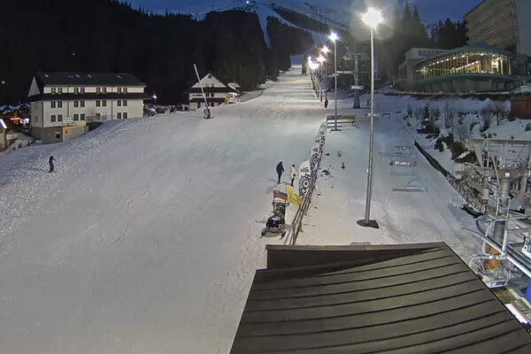 Štvrtok v Jasnej. Ľudia sa prechádzajú po zjazdovke, ešte funguje večerné lyžovanie.