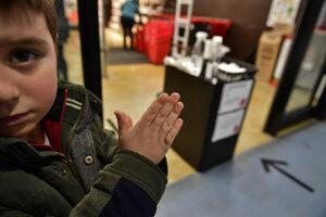 Chlapec si čistí ruky pred vstupom do obchodu v španielskej Pamplone.