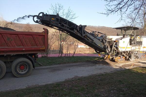 Vrchnú vrstvu asfaltu odvážali nákladné autá.