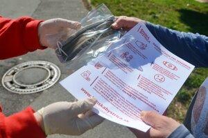 Zamestnankyňa Mestského úradu v Banskej Bystrici odovzdáva rúško a informačný leták dôchodkyni počas rozvozu ochranných rúšok určených pre dôchodcov.