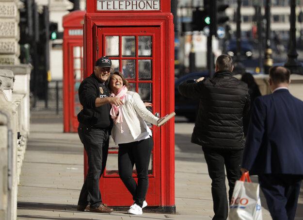 Dvaja turisti sa fotografujú pred tradičnou červenou telefónnou búdkou v Londýne.
