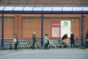 Ľudia zachovávajú odporúčané vzdialenosti pri čakaní v rade pred supermarketom Sainsbury's v anglickom meste Colton.