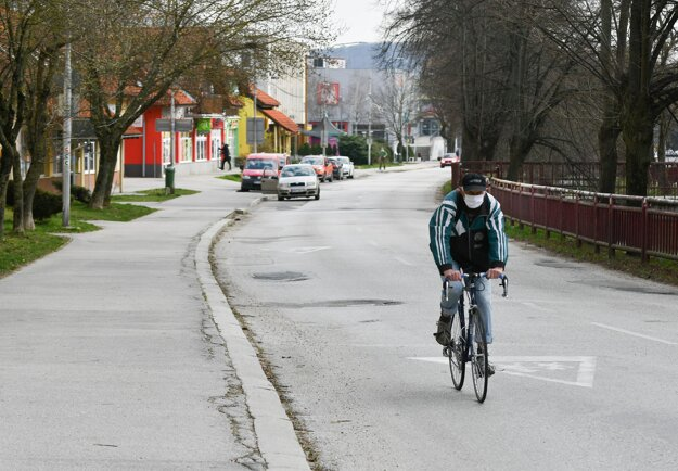 Cyklista s ochranným rúškom na tvári prechádza po ulici SNP v Starej Turej počas mimoriadnej situácie.