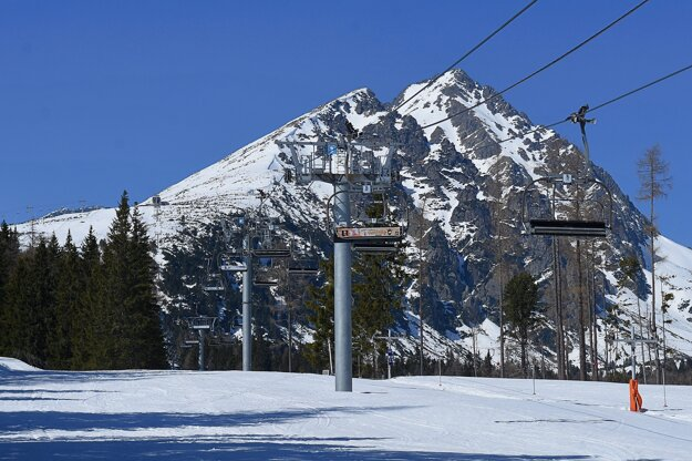 Prázdna sedačková lanovka a zjazdovka bez lyžiarov na Štrbskom Plese vo Vysokých Tatrách.