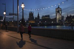 Chodci pri rieke Temža v Londýne.