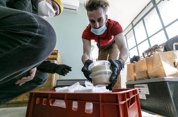 Dobrovoľníci pripravujú jedlá na rozvoz.