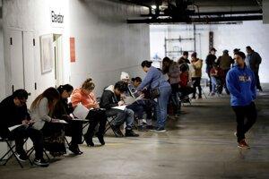Na fotografii z 13. marca 2020 ľudia čakajú v rade v garáži, aby požiadali o dávky v nezamestnanosti v Hospitality Training Academy v meste Los Angeles.