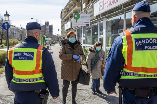 Policajti kráčajú pred ženami s ochrannými rúškami v maďarskom meste Békešská Čaba.