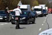 Policajná hliadka počas kontroly vodičov na ceste.