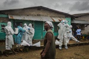 Pracovníci červeného kríža sa pripravujú vyniesť a pochovať telo muža, ktorý mal príznaky spojené s ebolou. Záber vznikol 20. apríla 2015 v libérijskej Monrovii. Pochádza zo série fotografií ocenenej Pulitzerovou cenou.