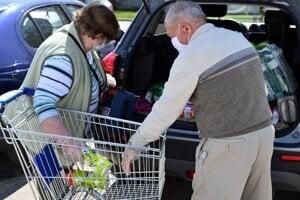 Koronavírus na Slovensku: Seniori si vykladajú nákup do auta vo vyhradenom čase pre seniorov nad 65 rokov od 09.00 do 12.00 hodiny na parkovisku pred supermarketom v meste Sečovce.