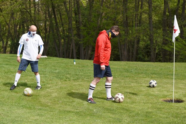 Footgolfisti so šatkami na tvári na footgolfovom ihrisku v Trnave.