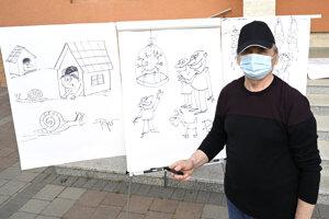 Na snímke karikaturista Vladimír Pavlík pózuje pred vtipmi, ktoré nakreslil pred Mestským kultúrnym strediskom v Novom Meste nad Váhom
