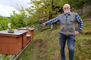 Včelár ukazuje na úľ, ktorý poškrabal medveď.