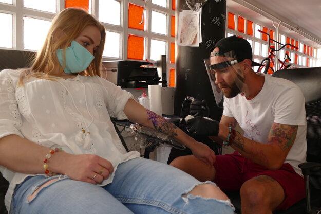 Tatér a jeho prvá zákazníčka po uvoľnení opatrení v tetovacom štúdiu v Žiline.