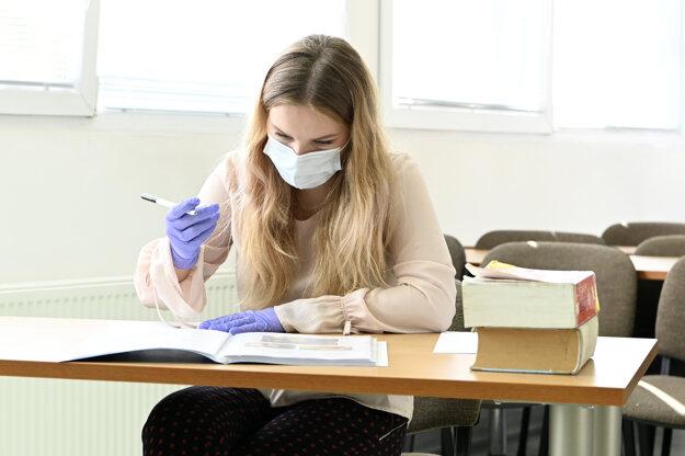 Študentka v ochrannom rúšku a ochranných rukaviciach sa pripravuje na odpoveď počas ústnej maturitnej skúšky, 25. mája 2020 na Strednej zdravotníckej škole Celestíny Šimurkovej v Trenčíne.