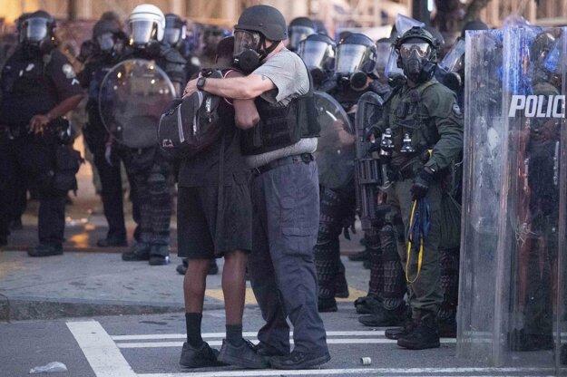 Policajt sa objíma s demonštrantom v Atlante.