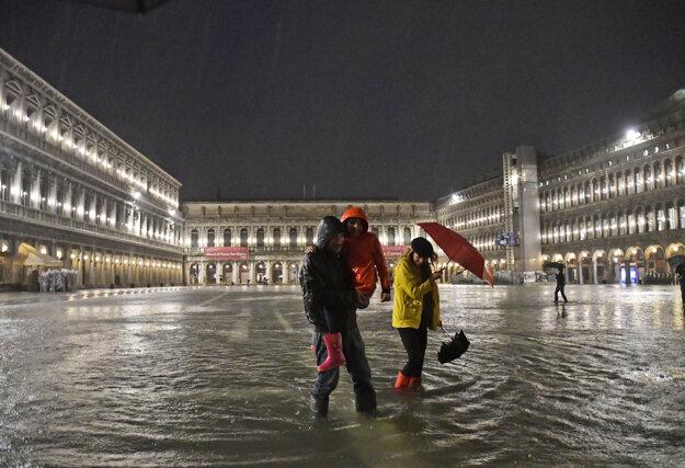 Ľudia prechádzajú po zaplavenom Námestí sv. Marka v Benátkach.