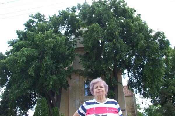 Helena Kukučková pred kostolom a vzácnymi lipami.