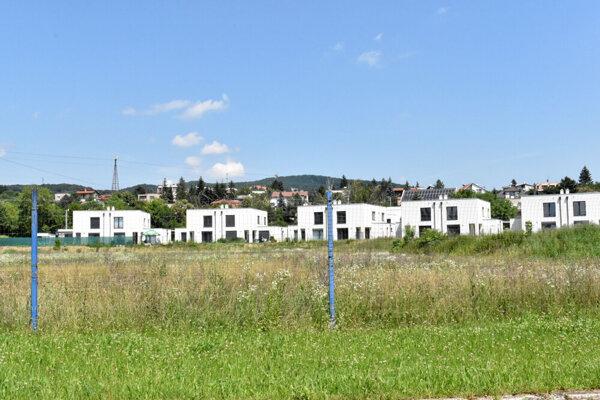 Na ploche dvoch tréningových ihrísk rastie burina. V pozadí stojí 5 apartmánových domov, ktoré športovcom neslúžia.