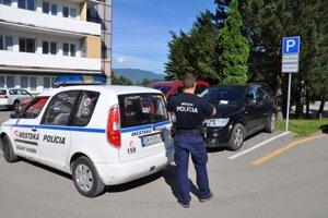 Mestskí policajt dokumentuje nesprávne parkovanie v areáli nemocnice.