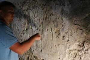 Archeológ Matúš Hudák ukazuje historické grafity na stenách bývalého hostinca.