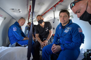 Astronauti Bob Behnken (v modrom vpredu) a Doug Hurley (v modrom vzadu) po pristáti.