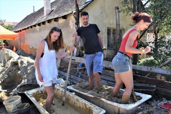 Príprava hliny na hlinenú omietku počas Letnej školy remesiel vo Vidinej.