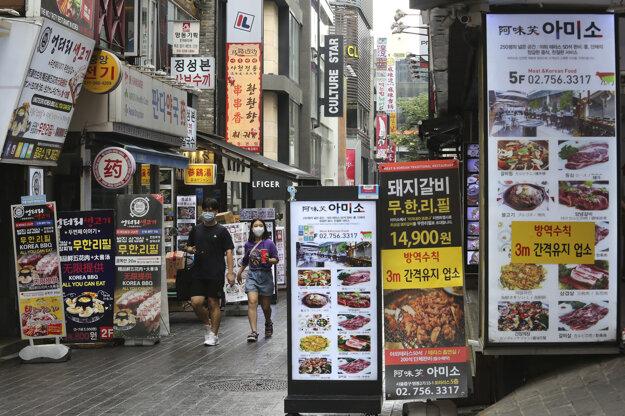 Chodci prechádzajú prázdnym centrom Soulu.