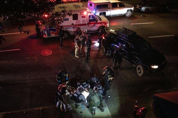 Záchranári ošetrujú postreleného muža.