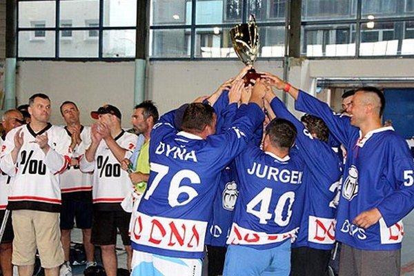 Víťazný pohár zdvihli nad hlavu hráči DoDna, vľavo strieborné Promile.