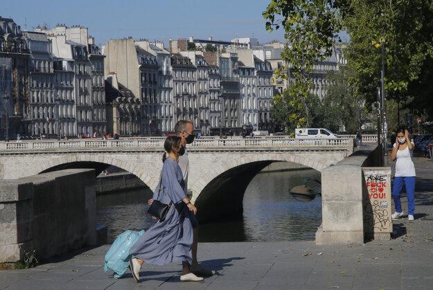 Koronavírus vo svete: Ľudia s ochrannými rúškami kráčajú pri brehu Seiny v Paríži.