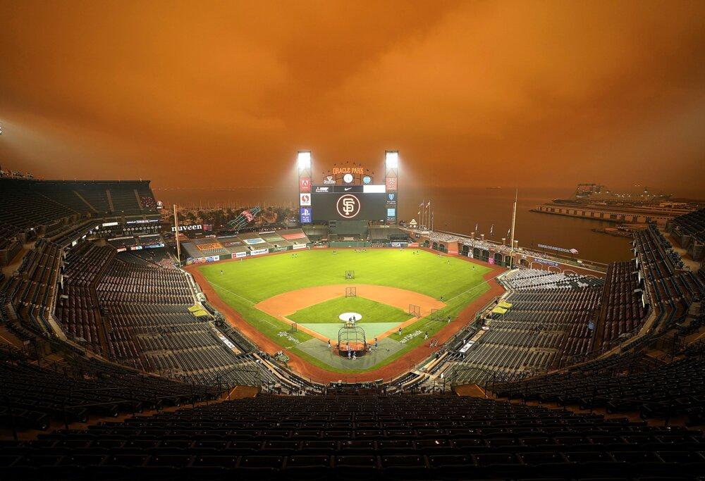 Hráči bejzbalového tímu Seattle Mariners trénujú na štadióne  Oracle Park pod oranžovou oblohou, zafarbenou od rozsiahlych požiarov.