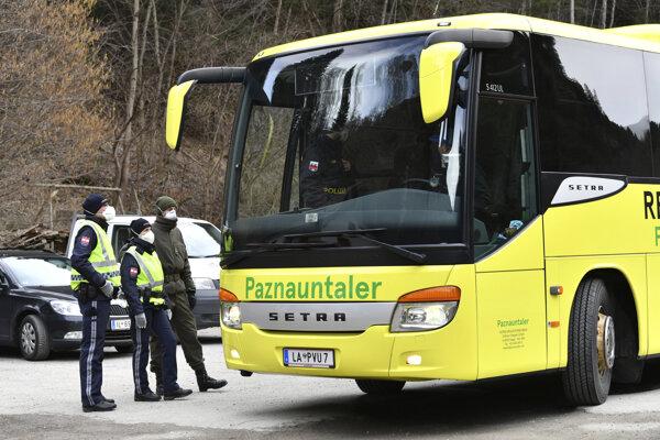Policajti kontrolujú autobus v tirolskej oblasti Paznauntal pri Landecku 14. marca 2020.