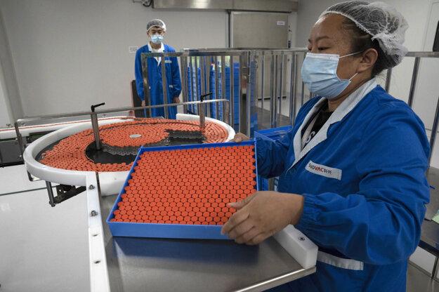 Výskumní pracovníci v továrni na výrobu vakcín SinoVac v Pekingu.