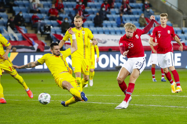 Erling Braut Haaland (Nórsko) strieľa gól v zápase Rumunsko - Nórsko v Lige národov. Bráni Andrei Burca (Rumunsko).