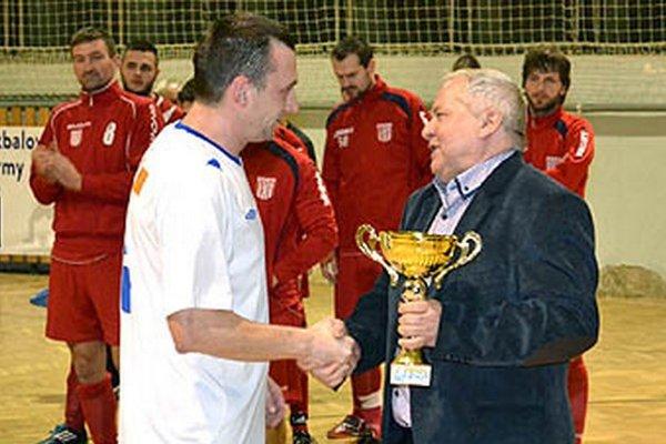 Pohár firmy TIBI si z rúk Tibora Rábeka odniesli futbalisti Horných Salíb. Gratuláciu prijíma kapitán Martin Bobor.