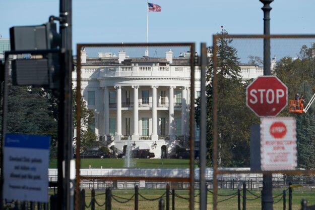 Biely dom je obkolesený vysokým plotom.