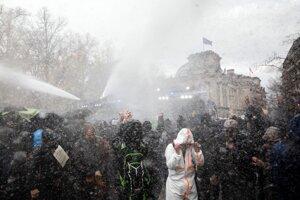 Polícia používa vodné delo na ľudí, ktorí protestujú pred Brandeburskou bránou v Berlíne proti plánom kancelárky Angely Merkelovej dať vláde právomoc na vymáhanie reštrikcií zacielených na obmedzenie šírenia nového druhu koronavírusu 18. novembra 2020.