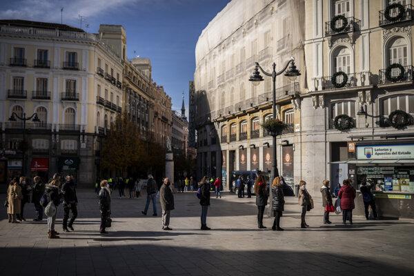 Ľudia čakajú v rade pred stánkom v centre Madridu, aby sa zapojili do španielskej vianočnej lotérie.
