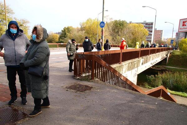 Ľudia čakajúci na moste pred odberným miestom na Námestí republiky v bratislavskej Petržalke 31. októbra 2020.